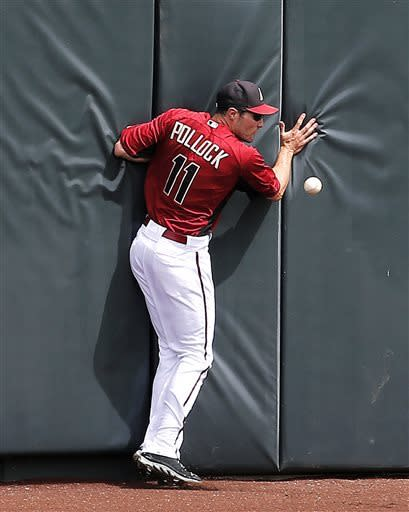 Arizona Diamondbacks' A.J. Pollock (11) hits the wall trying to catch a ball hit for an RBI triple by San Francisco Giants' Nick Noonan during the second inning of a spring training exhibition baseball game, Wednesday, March 27, 2013, in Scottsdale, Ariz. (AP Photo/Matt York)