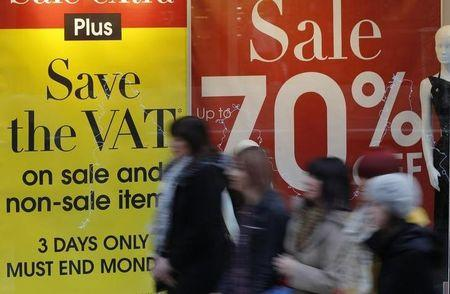 FILE PHOTO - People walk past sale signs in a shop window in Manchester