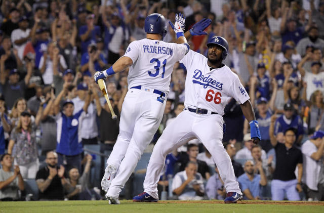 Los Angeles Dodgers' Yasiel Puig, right, celebrates with Joc Pederson afters scoring on a sacrifice by Pederson during the sixth inning against the San Francisco Giants in a baseball game Wednesday, Aug. 15, 2018, in Los Angeles. (AP Photo/Mark J. Terrill)