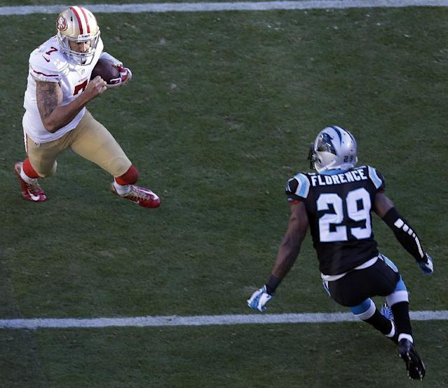 San Francisco 49ers quarterback Colin Kaepernick (7) heads into the end zone for a touchdown against Carolina Panthers cornerback Drayton Florence (29) during the second half of a divisional playoff NFL football game, Sunday, Jan. 12, 2014, in Charlotte, N.C. (AP Photo/Gerry Broome)