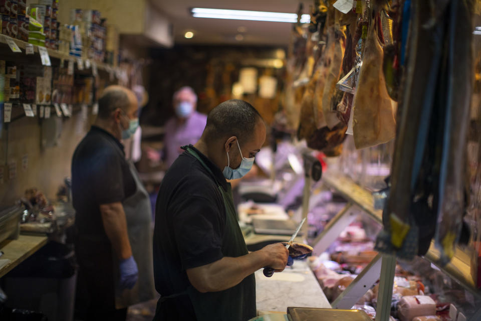 A worker wearing a face mask to prevent the spread of coronavirus cuts a piece of ham in downtown Madrid, Spain, Friday, Oct. 9, 2020. Spanish Prime Minister Pedro Sánchez is holding a Cabinet meeting to consider declaring a state of emergency for Madrid in order to impose stronger anti-virus restrictions on reluctant regional authorities. (AP Photo/Manu Fernandez)