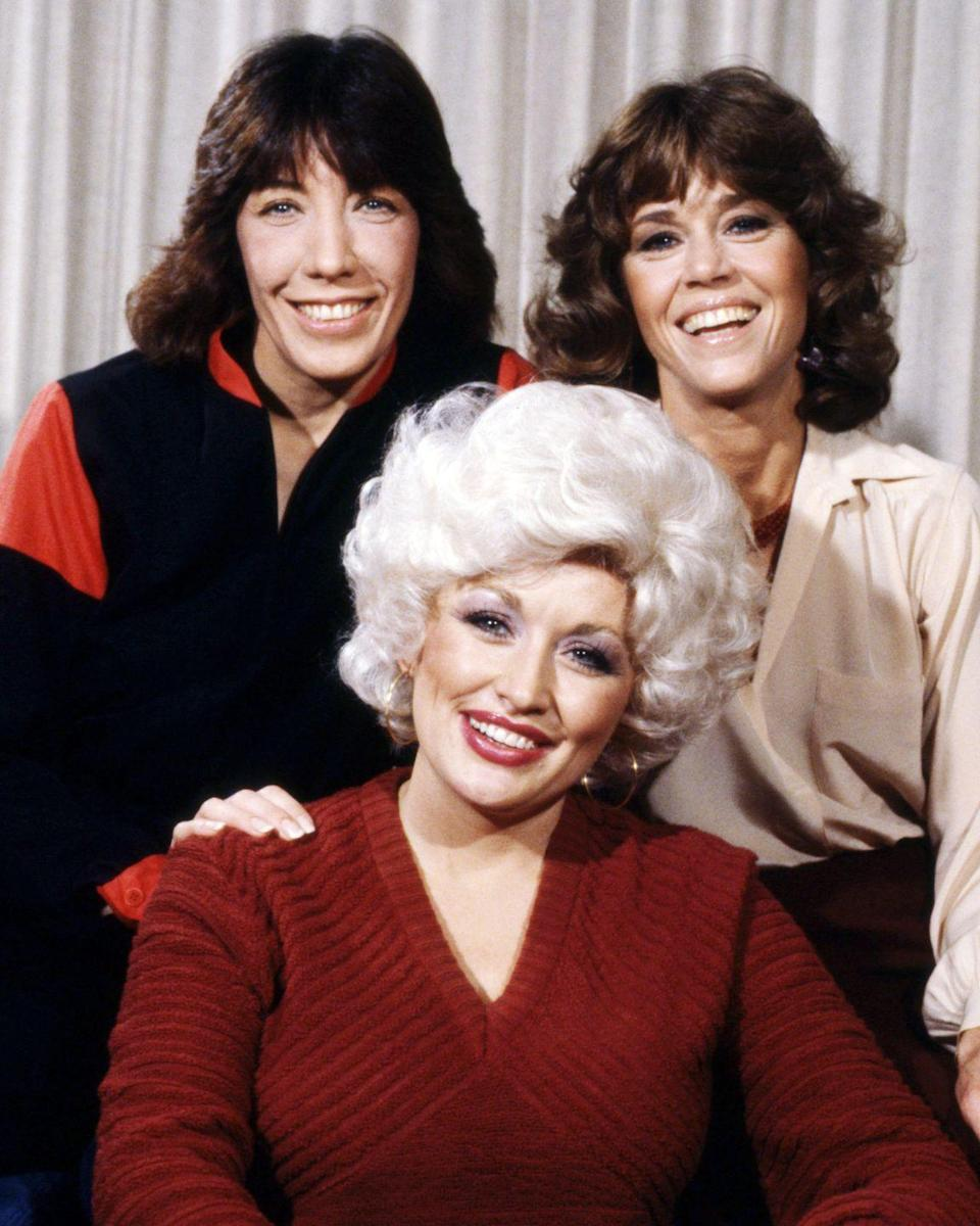 """<p>Parton trades in her sparkles for sweaters. Along with co-stars Lily Tomlin and Jane Fonda, Parton speaks to a new era of working women in the <a href=""""https://www.amazon.com/9-5-Jane-Fonda/dp/B005SAYWD8/ref=sr_1_1?crid=2M0DXJMQ72B2O&keywords=9+to+5&qid=1577998716&s=instant-video&sprefix=9+to+5%2Cinstant-video%2C154&sr=1-1&tag=syn-yahoo-20&ascsubtag=%5Bartid%7C1782.g.35034126%5Bsrc%7Cyahoo-us"""" rel=""""nofollow noopener"""" target=""""_blank"""" data-ylk=""""slk:groundbreaking movie, 9 to 5"""" class=""""link rapid-noclick-resp"""">groundbreaking movie, <em>9 to 5</em></a>. </p>"""