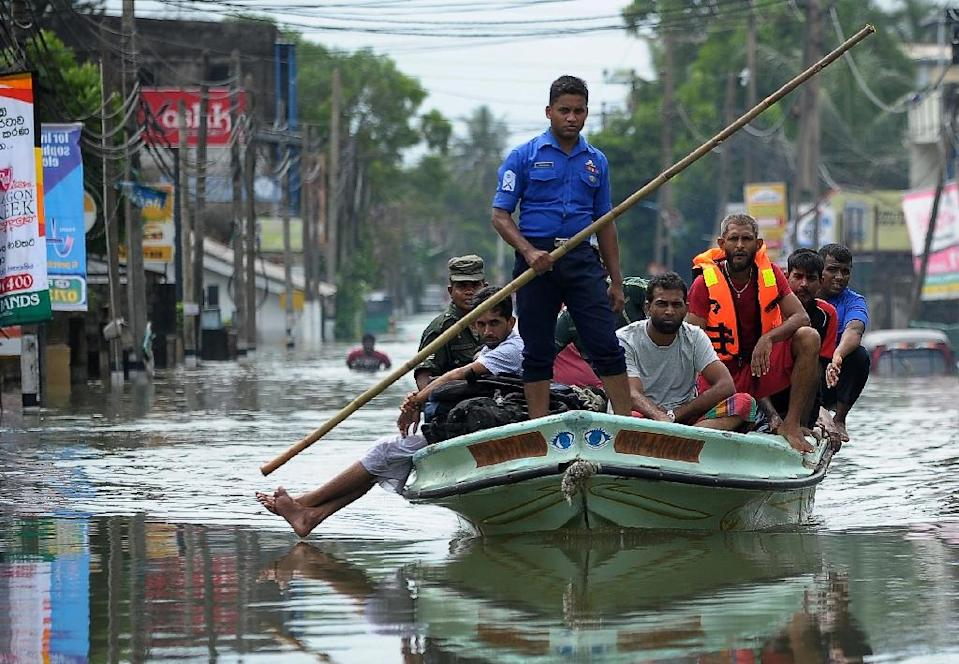 Sri Lankan rescue workers evacuate residents following flooding in the Kolonnawa suburb of Colombo, on May 20, 2016 (AFP Photo/Ishara S. Kodikara)