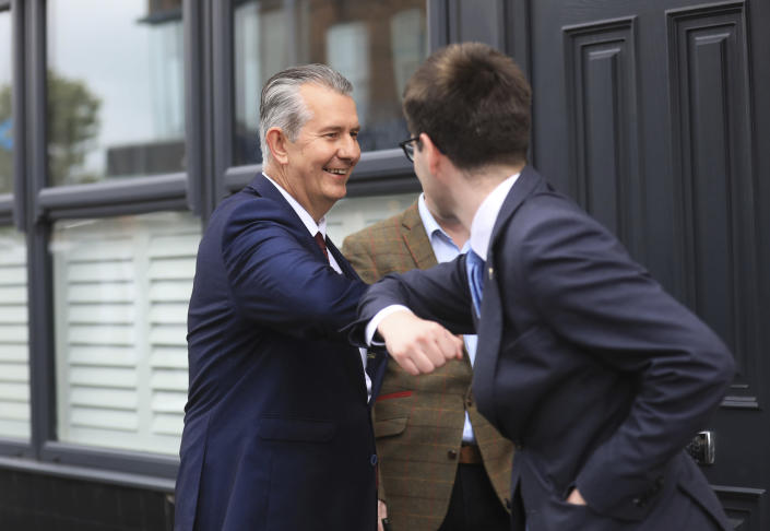 Democratic Unionist Party members Edwin Poots, left, is greeted by a supporter on the Belmont road after leaving the party headquarters in east Belfast after voting took place to elect a new leader on Friday May 14, 2021. Edwin Poots and Jeffrey Donaldson are running to replace Arlene Foster. (AP Photo/Peter Morrison)