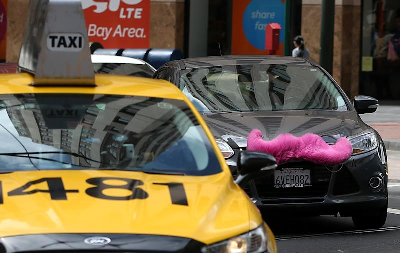 """A San Francisco taxi competes alongside a car run by Lyft, an Uber-like online cab service that along with other forms of the """"sharing economy"""" is on the rise"""