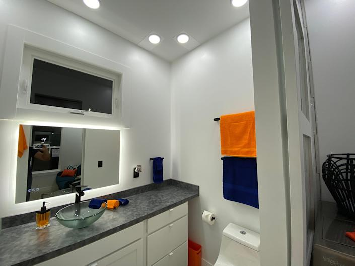 the bathroom with a toilet, sink, mirror
