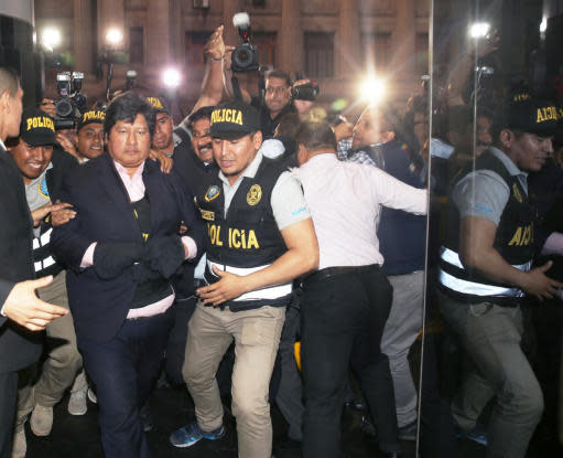 In this photo provided by Peru's Justice Palace press office, Peru's Football Federation President Edwin Oviedo is lead to jail in handcuffs in Lima, Peru, Thursday, Dec. 6, 2018. Oviedo, who was arrested a few months after leading his country back to the World Cup for the first time in 36 years, will be held initially for 15 days as prosecutors investigate his alleged connections to a criminal network that paid for several judges to attend the World Cup in Russia. (Francisco Medina/Peru's Justice Palace via AP)