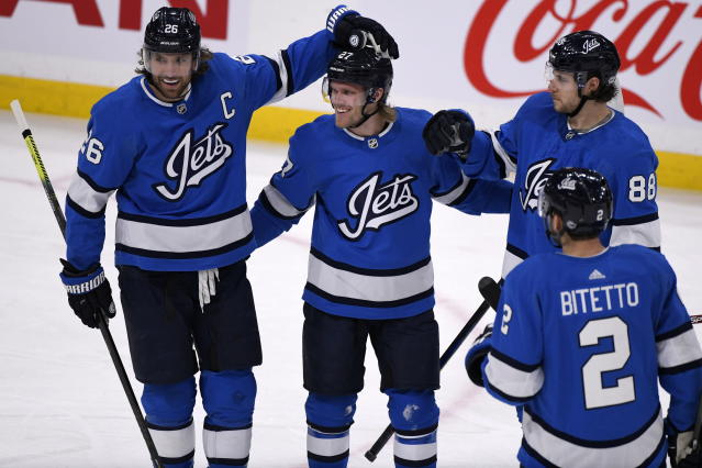 Winnipeg Jets' Nikolaj Ehlers (27) celebrates his goal against the Philadelphia Flyers with teammates Blake Wheeler (26), Nathan Beaulieu (88), and Anthony Bitetto (2) during first-period NHL hockey game action in Winnipeg, Manitoba, Sunday, Dec. 15, 2019. (Fred Greenslade/The Canadian Press via AP)