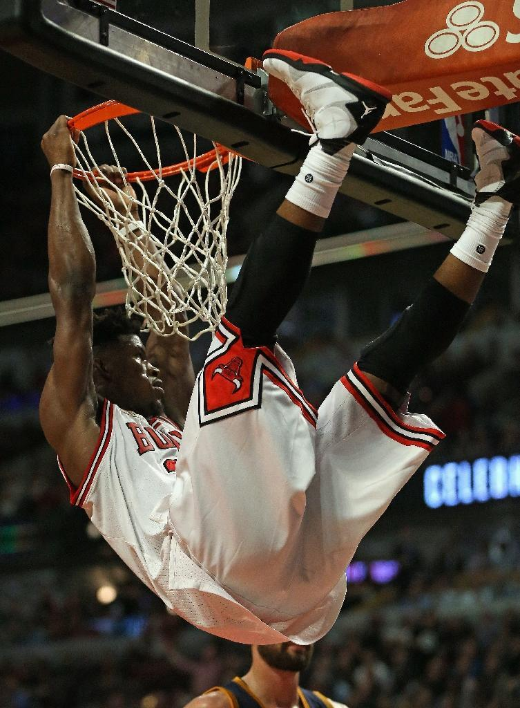 Chicago Bulls' Jimmy Butler hangs onto the rim after a dunk during the season opening game against the Cleveland Cavaliers at United Center on October 27, 2015 (AFP Photo/Jonathan Daniel)