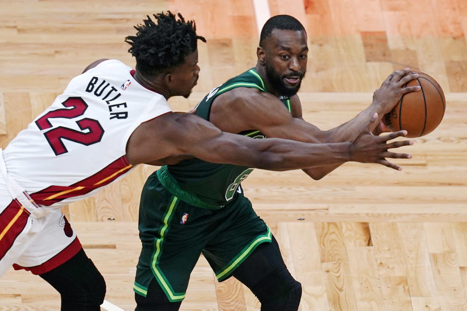 Miami Heat forward Jimmy Butler (22) tries to block a pass by Boston Celtics guard Kemba Walker during the first half of an NBA basketball game Tuesday, May 11, 2021, in Boston. (AP Photo/Charles Krupa)