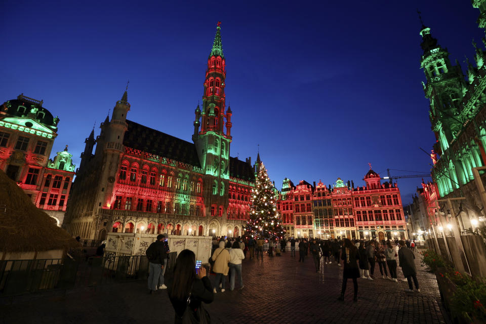 FILE - In this Tuesday, Nov. 24, 2020 file photo, people walk in the historic Grand Place during the official lighting of the Christmas tree in Brussels. Nations are struggling to reconcile cold medical advice with a holiday tradition that calls for big gatherings in often poorly ventilated rooms, where people chat, shout and sing together, providing an ideal conduit for a virus that has killed over 350,000 people in Europe so far. (AP Photo/Olivier Matthys, File)