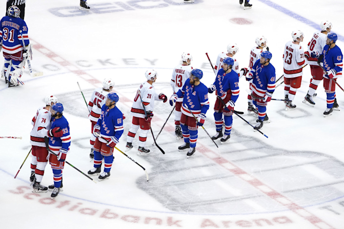 Members of the Carolina Hurricanes and New York Rangers at the conclusion of their Stanley Cup playoff series Aug. 4.