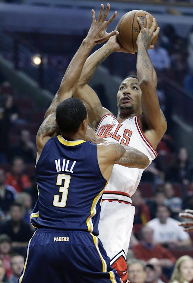 Chicago Bulls guard Derrick Rose (1) goes up for a shot against Indiana Pacers guard George Hill (3) during the first half of an NBA preseason basketball game in Chicago on Friday, Oct. 18, 2013. (AP Photo/Nam Y. Huh)