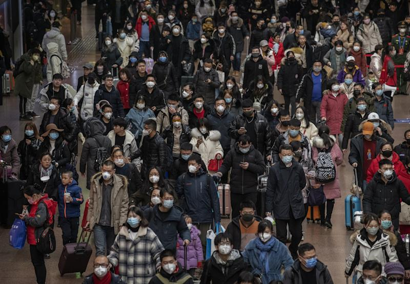 Chinese passengers, most wearing masks, arrive to board trains before the annual spring festival at a Beijing railway station on 23 January 2020: Getty