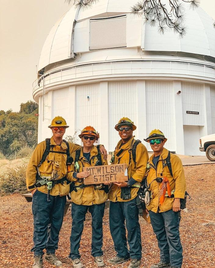 Firefighters from Monrovia, Calif., pose in front of the historic Mount Wilson Observatory after working to protect the 116-year-old structure from the Bobcat Fire.