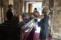 A woman places a flower on a coffin as people pay their final respect to the late composer Mikis Theodorakis, in Athens, on Monday Sept. 6, 2021. Hundreds of people have gathered outside Athens Cathedral where Greek composer and politician Mikis Theodorakis is to lie in state in a chapel of the cathedral for three days ahead of his burial on the southern island of Crete. (AP Photo/Petros Giannakouris)