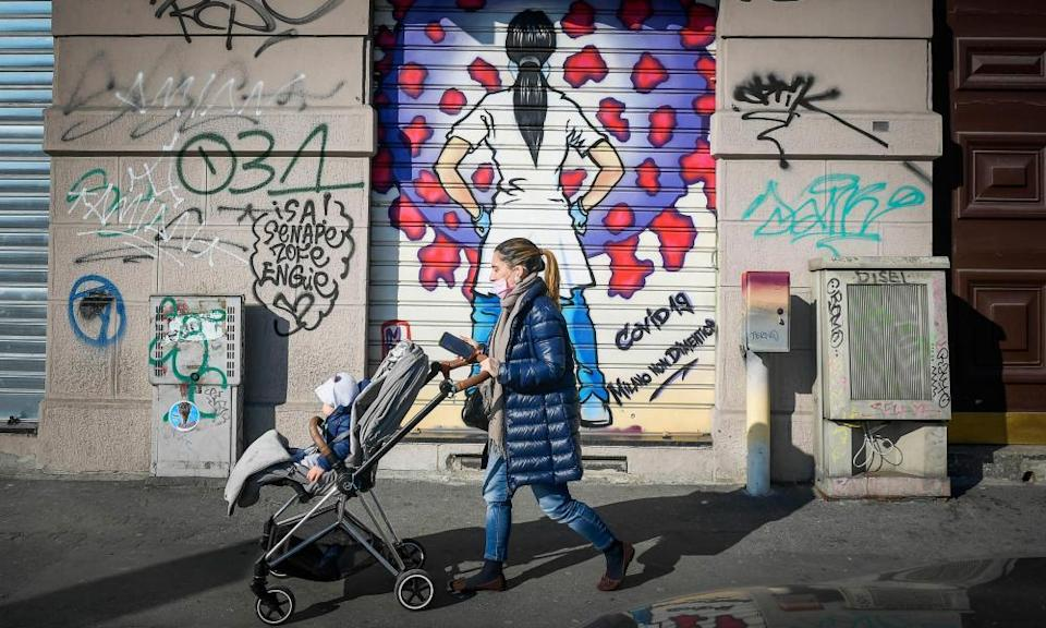 A woman and her child pass Covid-19 street artwork on the shutter of a shop in Milan.