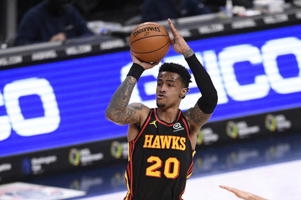 John Collins shoots the ball during a game.