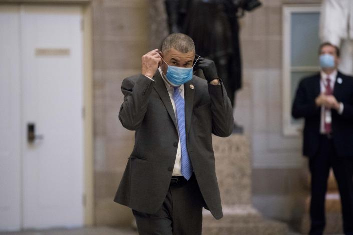 """FILE - In this April 23, 2020, file photo, Rep. William Lacy Clay, D-Mo., puts on his mask as he walks towards the House Chamber on Capitol Hill, in Washington. National lawmakers are expected on Wednesday to introduce a joint resolution aimed at striking language from the U.S. Constitution that enshrines a form of slavery in America's foundational documents. A House version is led by outgoing Clay, who said the amendment """"seeks to finish the job that President (Abraham) Lincoln started."""" (AP Photo/Andrew Harnik, File)"""