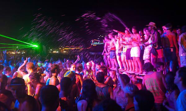 People dancing at the Full Moon Party on Haad Rin beach Koh Phangan Thailand