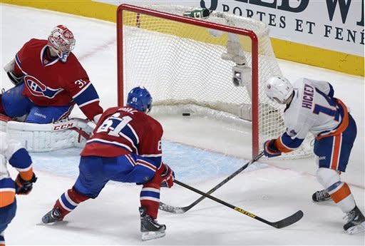 Montreal Canadiens goaltender Carey Price (31) is scored on by New York Islanders' Thomas Hickey, right, as Canadiens' Raphael Diaz defends during overtime of their NHL hockey game, Thursday, Feb. 21, 2013, in Montreal. The Islanders won 4-3. (AP Photo/The Canadian Press, Graham Hughes)