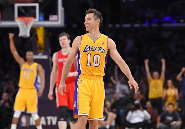 Los Angeles Lakers' Steve Nash, center, smiles after picking up an assist to take sole possession of third place for NBA all-time assists, during the first half of an NBA basketball game against the Houston Rockets, Tuesday, April 8, 2014, in Los Angeles. (AP Photo/Mark J. Terrill)