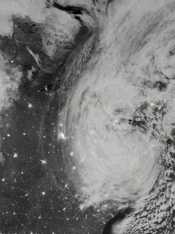 """The Visible Infrared Imaging Radiometer Suite (VIIRS) on the Suomi NPP satellite acquired this image of Hurricane Sandy around 3:35 a.m. Eastern Daylight Time (7:35 Universal Time) on October 30. This image is from the """"day-night band"""" on VIIRS, which detects light wavelengths from green to near-infrared. The full Moon, which exacerbated the height of the storm water surge, lit the tops of the clouds. (NASA)"""