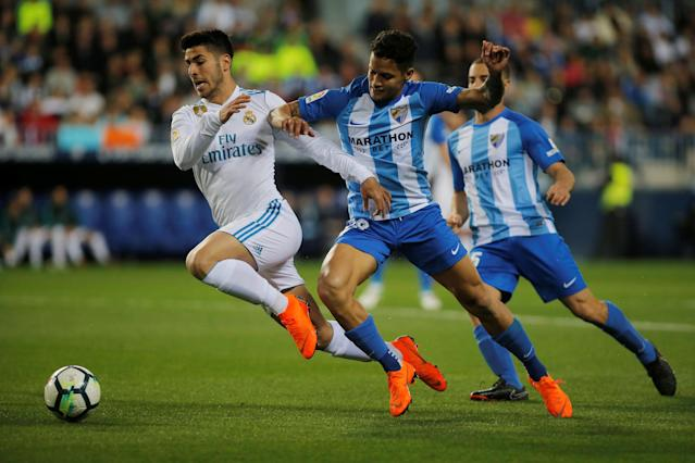 Soccer Football - La Liga Santander - Malaga CF vs Real Madrid - La Rosaleda, Malaga, Spain - April 15, 2018 Real Madrid's Marco Asensio in action with Malaga's Roberto Rosales REUTERS/Jon Nazca