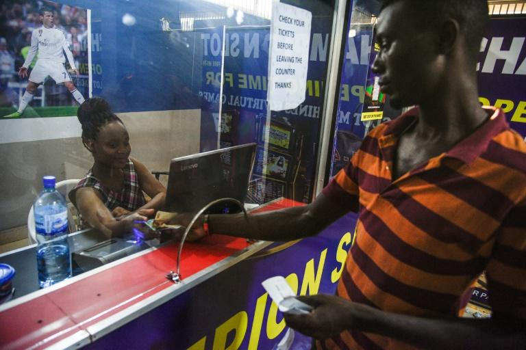 A gambler picks up winnings of 15,000 Ugandan shilling (just under $4) -- he had bet 50,000 shillings on Russia beating Saudi Arabia in the World Cup's opening match