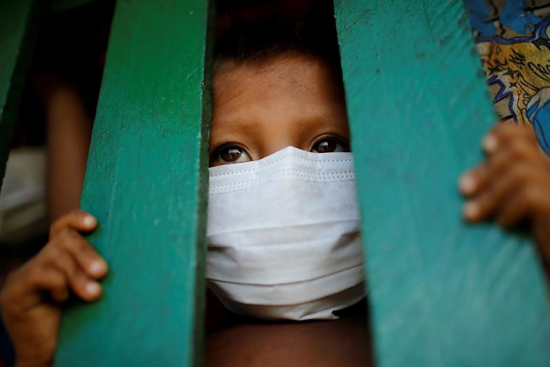 A child from the indigenous Yanomami ethnic group wearing protective face mask looks on, amid the spread of the coronavirus disease (COVID-19), at the 5th Special Frontier Platoon in the municipality of Auaris, state of Roraima, Brazil June 30, 2020. REUTERS/Adriano Machado TPX IMAGES OF THE DAY