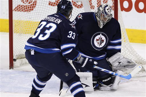 New York Islanders' Josh Bailey's (not shown) shot blasts past Winnipeg Jets' goaltender Ondrej Pavelec (31) and Dustin Byfuglien (33) during the first period of an NHL hockey game in Winnipeg, Manitoba, Saturday, April 20, 2013. (AP Photo/The Canadian Press, John Woods)