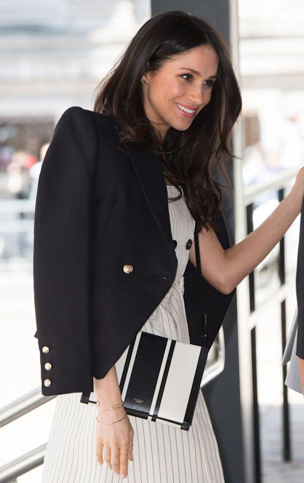 "<p>On 18 April 2018, Meghan Markle gave the nation a glimpse of her future role within the royal family. Decked in a spring-ready pinstripe dress by Altuzarra, the then bride-to-be accessorised the look with a cross-body bag by Aussie label, Oroton. The Avalon zip-up number retails at £171 and we need to get our hands on it, asap. <a rel=""nofollow"" href=""https://www.oroton.com.au/avalon-zip-top-crossbody-black-cream-mix-osfa""><em>Shop now</em></a>. </p>"