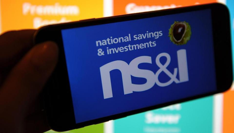 The National Savings & Investments logo on a phone and the website on a computer