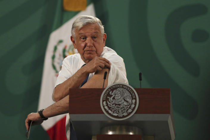 Mexican President Andres Manuel Lopez Obrador shows the spot where he had just gotten a shot of the AstraZeneca vaccine for COVID-19 during his daily, morning news conference at the presidential palace in Mexico City, Tuesday, April 20, 2021. (AP Photo/Fernando Llano)