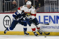 Florida Panthers' Aleksander Barkov (16) moves the puck past Tampa Bay Lightning's Ondrej Palat (18) during the first period of an NHL preseason hockey game, Tuesday, Oct. 5, 2021, in Orlando, Fla. (AP Photo/John Raoux)