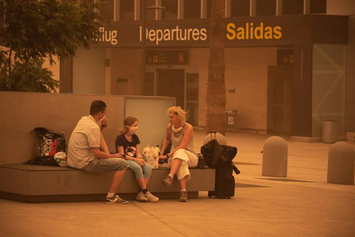 Passengers wait outside Tenerife SouthReina Sofia Airport after flights were cancelled due to a sandstorm on February 23, 2020 on the Canary Island of Tenerife.