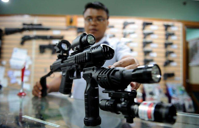 A salesman at a weapons shop in Manila demonstrates how to use a conversion kit on a 9mm handgun on April 4, 2013