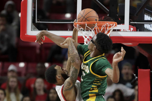 Maryland guard Eric Ayala, left, dunks on George Mason forward AJ Wilson during the first half of an NCAA college basketball game Friday, Nov. 22, 2019, in College Park, Md. (AP Photo/Julio Cortez)