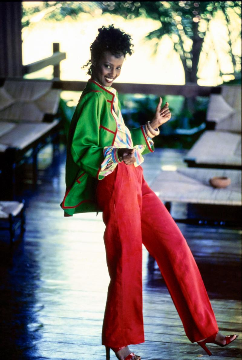 Model Iman wearing an ensemble from Ungaro: a green cotton jacket with red piping; narrow red cotton pants; multi-color striped silk shirt tied at the waist. Styled with a hair comb by Bill Schiffer for Schiffer Aesthetics, bangles from Borbonese for Ungaro Jewelry, and red three-inch mules from Geoffrey Beene. Hair by Marc Pipino for Pipino-Buccheri Salon. Makeup by Sandra of Xavier New York. Photographed at the home of Oscar and Françoise de la Renta in La Romana, Dominican Republic, about 90 minutes from Santo Domingo.