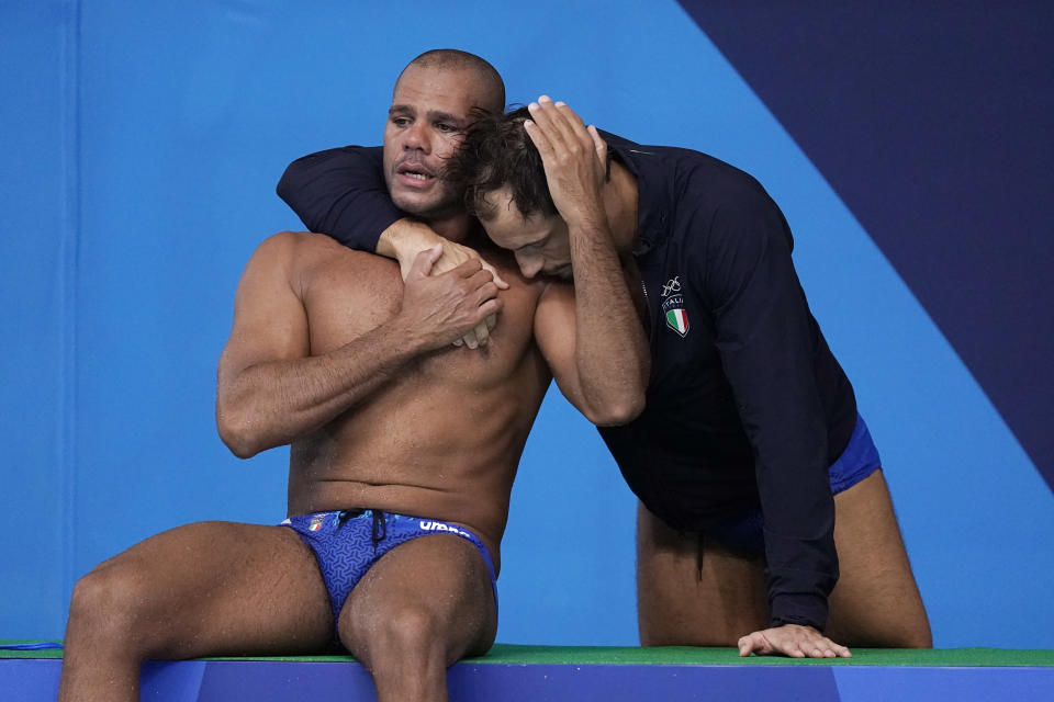 Italy's Michael Alexandre Bodegas, left, is comforted by teammate Matteo Aicardi after a loss to Serbia in a quarterfinal round men's water polo match at the 2020 Summer Olympics, Wednesday, Aug. 4, 2021, in Tokyo, Japan. (AP Photo/Mark Humphrey)