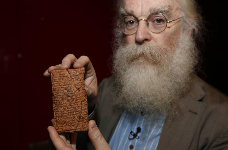 Irving Finkel, curator in charge of cuneiform clay tablets at the British Museum, poses with the 4000 year old clay tablet containing the story of the Ark and the flood during the launch of his book 'The Ark Before Noah' at the British Museum in London, Friday, Jan. 24, 2014. The book tells how he decoded the story of the Flood and offers a new understanding of the Old Testament's central narratives and how the flood story entered into it. (AP Photo/Sang Tan)