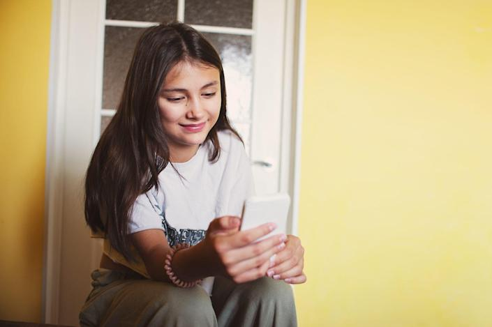 An image of a teen on their phone.