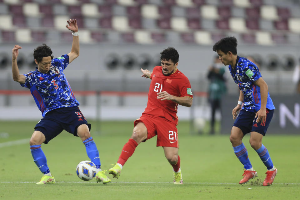 Japan's Sei Muroya, left, and Aloisio Goncalves ight for possession during a FIFA World Cup qualifying soccer match between China and Japan in Doha, Qatar, Tuesday, Sept. 7, 2021. (AP Photo/Hussein Sayed)