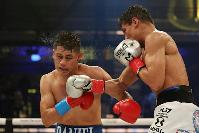 Murodjon Akhmadaliev lands a punch en route to a split decision victory over Daniel Roman to claim the WBA and IBF 122 pound boxing title in Miami (AFP Photo/Michael Reaves)