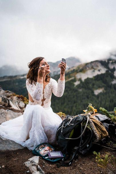 PHOTO: A bride touches up her makeup on a mountaintop during an adventure elopement. (Thefoxesphotography.com)