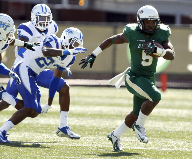 CORRECTS DATE TO NOV. 2, NOT NOV. 1 - UAB running back Darrin Reaves escapes the tackle of Middle Tennessee State cornerback Chris Sharpe and runs for a first down during the first half of an NCAA college football game on Saturday, Nov. 2, 2013, in Birmingham, Ala. (AP Photo/Butch Dill)