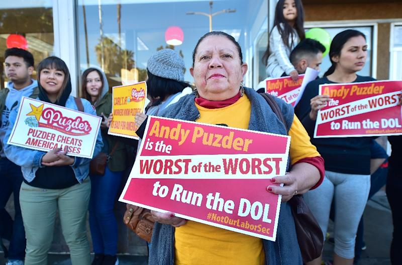Fast-food workers hold placards and shout slogans protesting against fast food mogul Andy Puzder as President Donald Trump's nominee for labor secretary in January 2017 in Los Angeles , California (AFP Photo/Frederic J. BROWN)
