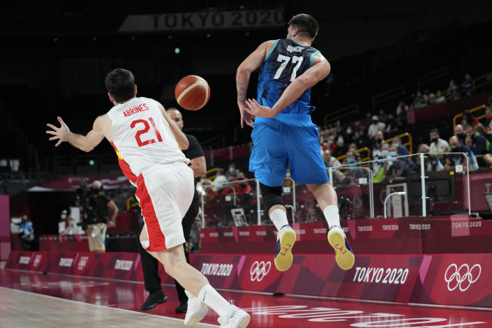 Slovenia's Luka Doncic (77) passes the ball past Spain's Alejandro Abrines Redondo (21) as he goes out of bounds during a men's basketball preliminary round game at the 2020 Summer Olympics, Sunday, Aug. 1, 2021, in Saitama, Japan. (AP Photo/Eric Gay)