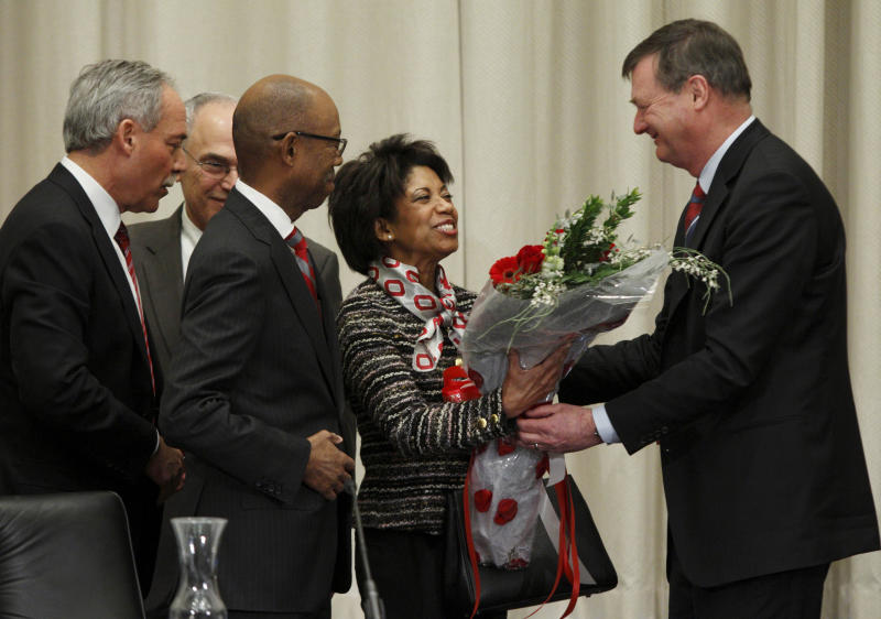 Ohio State University board trustee Jeffery Wadsworth, right, presents Brenda Drake, second from right, with flowers as her husband Dr. Michael Drake, third from right, looks on with board chair Robert Schottenstein, left, and interim university president Joseph Alutto after Dr. Drake was voted in as the incoming president of the university during a board meeting at the university Wednesday, Jan. 30, 2014. (AP Photo/Paul Vernon)