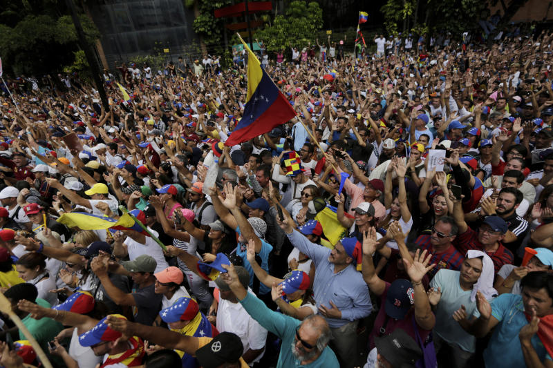 Anti-government protesters hold their hands up during the symbolic swearing-in of Juan Guaido, head of the opposition-run congress who declared himself interim president of Venezuela until elections can be called, during a rally demanding President Nicolas Maduro's resignation in Caracas, Venezuela, Wednesday, Jan. 23, 2019. Venezuela's crisis quickly escalated as the opposition leader backed by the Trump administration declared himself interim president in a direct challenge to Maduro, who retaliated by breaking off relations with the United States, his biggest trade partner. (AP Photo/Fernando Llano)